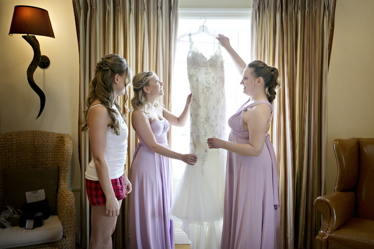 Bridesmaids helping with wedding dress