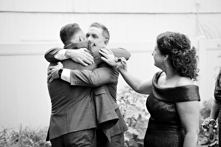 Dad hugging son after wedding ceremony